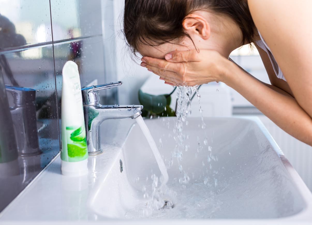 girl removing makeup washing face